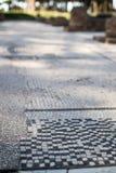 Romańska mozaika z małymi czarny i biały kamieniami tafluje representin Fotografia Stock