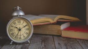 Romański liczebnik w rocznika budziku i Otwiera Książkowych tło wi fotografia stock