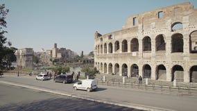 ROMA - 20 DE FEBRERO: Coches y turistas cerca de Roman Colosseum People en trajes almacen de metraje de vídeo
