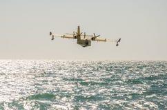 ROMA, ITÁLIA - EM JULHO DE 2017: Os aviões do sapador-bombeiro do céu extinguem um fogo que recolhe a água no mar Tyrrhenian pert Foto de Stock Royalty Free