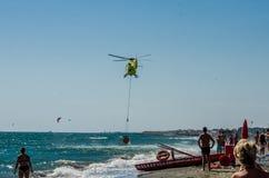 ROMA, ITÁLIA - EM JULHO DE 2017: Um helicóptero do fogo está pegarando a água em uma cesta para extinguir um fogo no mar Tyrrheni Fotografia de Stock