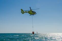 ROMA, ITÁLIA - EM JULHO DE 2017: Um helicóptero do fogo está pegarando a água em uma cesta para extinguir um fogo no mar Tyrrheni Foto de Stock