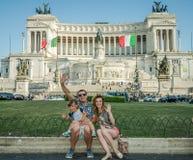 ROMA, ITÁLIA - EM JULHO DE 2017: Uma família feliz nova em uma excursão de Itália dá uma volta no quadrado de Veneza em Roma em u Fotografia de Stock