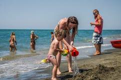 ROMA, ITÁLIA - EM JULHO DE 2017: Uma família, uma mãe e uma filha novas com uma natação circundam, jogando na praia na praia do T Foto de Stock Royalty Free