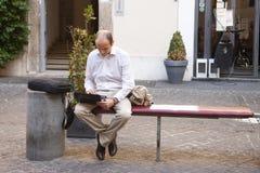 Roma, Itália, o 14 de outubro de 2011: Homem novo que senta-se em um banco da rua com um portátil fotografia de stock royalty free