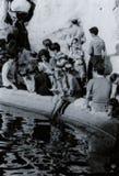 ROMA, ITÁLIA, 1970 - um turista fêmea novo, louro lê um livro quietamente ao refrescar seus pés na fonte do Trevi fotos de stock