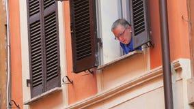ROMA - ITALIA, AGOSTO DE 2015: mujer italiana que mira de ventana metrajes