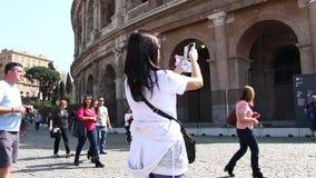 ROMA, ITALIA - 25 de marzo de 2017: Turistas del coliseo que toman la imagen vía el teléfono cerca de Colosseum en Roma almacen de metraje de vídeo