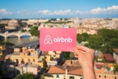 Roma, Italia - 13 de mayo de 2018: Persona que lleva a cabo el logotipo de Airbnb disponible con la ciudad en fondo imágenes de archivo libres de regalías