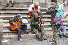 Roma, Italia, el 10 de octubre de 2011: Juego sin hogar la guitarra en los pasos de un templo católico fotografía de archivo