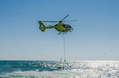 ROMA, ITALIA - JULIO DE 2017: Un helicóptero del fuego está cogiendo el agua en una cesta para extinguir un fuego en el mar tirre Imagen de archivo libre de regalías