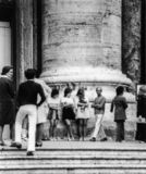Roma, Italia, 1970 - tre ragazze in minigonne riposano nella folla al piede di una colonna fotografia stock