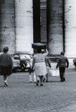 ROMA, ITALIA, 1970 - una famiglia degli emigranti cammina vicino alla colonnato della S Peter Square con una scatola di cartone e fotografia stock