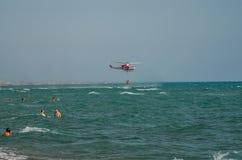 ROMA, ITALIE - JUILLET 2017 : L'hélicoptère de sapeur-pompier pendant l'opération de sauvetage recueille l'eau la mer tyrrhénienn Photographie stock