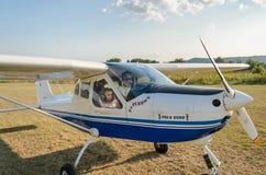 ROMA ITALIEN - AUGUSTI 2018: Ett erfaret barn för pilot och lite flickapå rodern av ettmotor flygplanTecnam P92 eko royaltyfria bilder