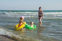 ROMA ITALIEN - JULI 2017: Liten charmig flicka som spelar på en sandig strand med en uppblåsbar cirkel med en flickvän och in sim Arkivfoton