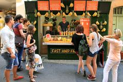 Aix-en-Provence, FRANCE - JULY 1, 2017. People near the stall with fresh fruit cocktails. Fresh pieces of fruit in glasses with m. Int on the top. Aix-en Stock Image