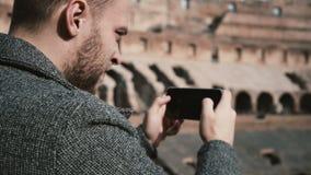 Roma, Italy-11 02 Hombre hermoso joven 2017 que se coloca dentro del Colosseum en Roma y que toma las fotos de ruinas en smartpho almacen de video