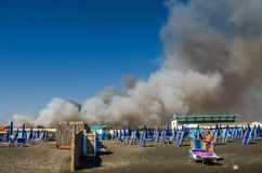 ROMA, ITALY - JULY 2017: Fire with smoke clouds on the beach with blue umbrellas and sun loungers in Ostia, Italy Stock Photography