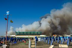 ROMA, ITALY - JULY 2017: Fire with smoke clouds on the beach with blue umbrellas and sun loungers in Ostia, Italy Stock Photo