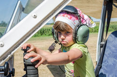 ROMA, ITALY - JULY 2017: Little charming little girl pilot, child in the cockpit of light-engine aircraft Tecnam P92-S Echo. Little charming little girl pilot Royalty Free Stock Photo