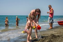 ROMA, ITALY - JULY 2017: A young family, mother and daughter with a swimming circle, playing on the beach on the beach of the Tyrr Royalty Free Stock Photo