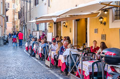 Roma, Italy - October 2015: Cafe restaurant on the ancient narrow street in Rome, Italy where eating and leisure travelers Royalty Free Stock Photos