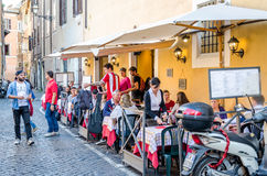 Roma, Italy - October 2015: Cafe restaurant on the ancient narrow street in Rome, Italy where eating and leisure travelers Stock Photos