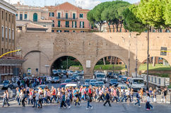 Roma, Italy - October 2015: A large crowd of pedestrians tourists passes through a pedestrian crossing a busy street with traffic Royalty Free Stock Photos