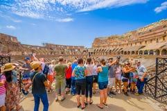 ROMA, ITÁLIA - 13 DE JUNHO DE 2015: Turists que aprecia Roman Coliseum interno, pessoa que toma fotografias e que visita este mun Fotos de Stock Royalty Free