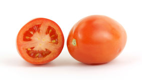 Roma single and cut. A nice view of a whole and sliced roma tomato Royalty Free Stock Images