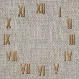 Romańskich liczebników zegar na burlap tkaniny tle Fotografia Stock