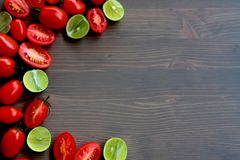 Roma Tomatoes and Key Limes on Grey Stained Wood Background Stock Image