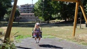 ROMA WŁOCHY, LIPIEC, - 2017: Mała powabna dziewczyna w chustce Hello Kitty jedzie na huśtawce w parku na boisku zbiory wideo
