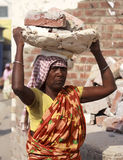 Roma woman carries bricks on his head. Royalty Free Stock Images