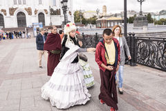 Roma women in ancient dresses make a fool of Tibetan monks at t Stock Images
