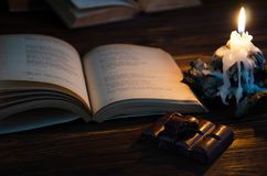 romaans Boek van gedichten, zwarte poreuze chocolade en een kaars royalty-vrije stock foto