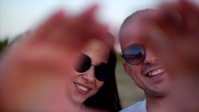 Romaans Concept, Jong Paar die, die en een hartvorm met hun handen aughing maken stock videobeelden