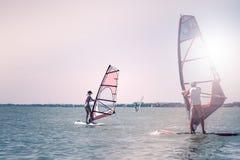Romaans in de overzeese paarman en de vrouw die samen op een windsurfing raad varen terwijl op vakantie in zuiden stock afbeeldingen