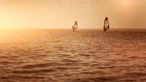 Romaans in de overzeese paarman en de vrouw die samen op een windsurfing raad varen terwijl op vakantie in zuiden stock afbeelding