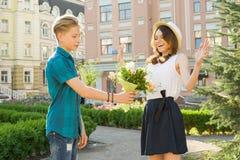 Romaans in paar van tienerjaren, de verrassingen van de tienerjongen geeft boeket in openlucht van bloemen aan zijn meisje Stock Foto