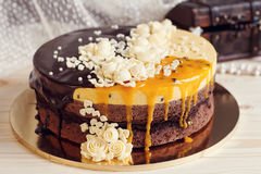 Romaantic cake with chocolate glaze, cream flowers and  mango pa Royalty Free Stock Photography