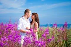 Romace onder purpere bloemen dichtbij blauwe overzees Stock Fotografie