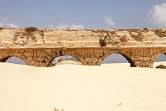 Roman Aqueduct At Caesaria. Remnants of the old Roman stone aqueduct that supplied water to the ancient cty of Caesaria, now in Israel. The sands of the beach Stock Photos
