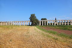 A Roman aqueduct on grassy meadow Stock Photography