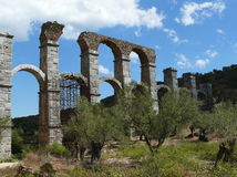 Roman aqueduct between olive trees. Lesvos. Greece. Remains of the excellent engineering art of the ancient empires. Roman aqueduct on the inhospitable land of stock image