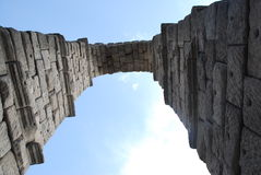 Roman Aqueduct Overhead Against Blue Sky. Stone arch of an ancient Roman Aquaduct as seen from under the arch Royalty Free Stock Photos