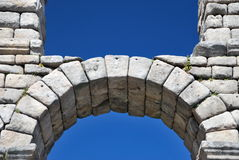 Roman arch. Detail of an old Roman arch over a blue sky Stock Photography