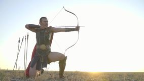 Roman archer in the field on a sunny afternoon, kneels, stretches bows, takes aim and shoots, slow motion
