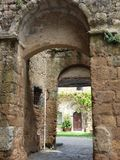 Roman arches leading to a wood door stock photography